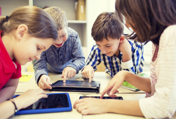 A group of three students, along with a teacher, sit around a table and play on tablets.
