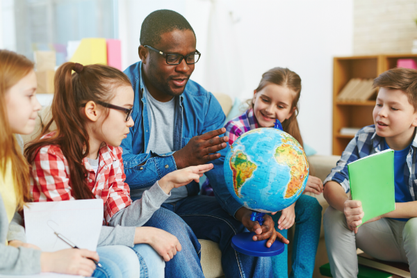 A teacher sits on a couch with students, using a globe to show them certain geographic locations.