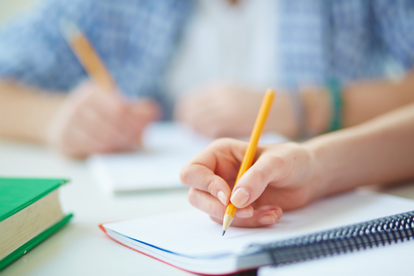 Two students sit at the same table, each using pencils to write in their workbooks.