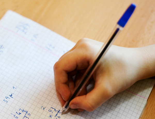 A student completes multiplication problems in blue pen on a sheet of graph paper.