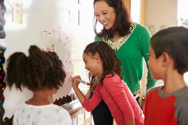 A teacher stands at her whiteboard with three students, one of which completes a math equation on the board.