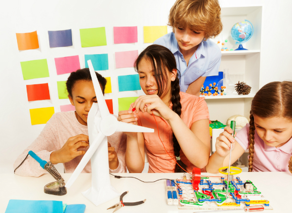 A group of four students work together to complete a project that involves constructing a model windmill.