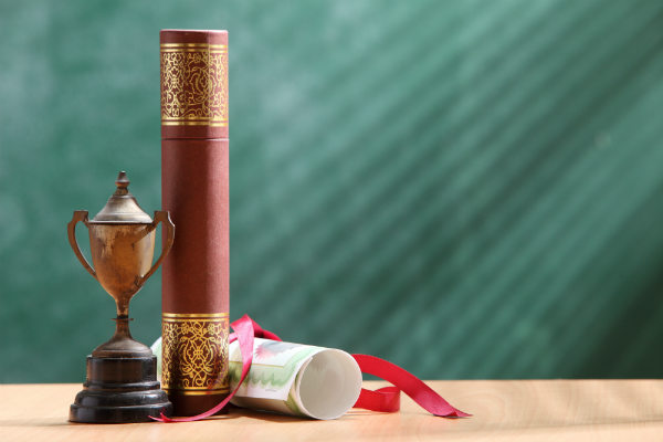 A trophy sits on a desk in front of a blackboard, smudged with erased chalk markings.