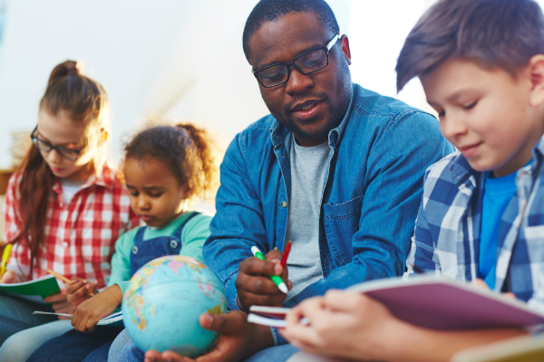 A teacher sits with his students, demonstrating concepts from a book using a globe.