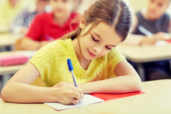 Math Word Problems - A female elementary students sits at her desk, writing in her notebook using pen.