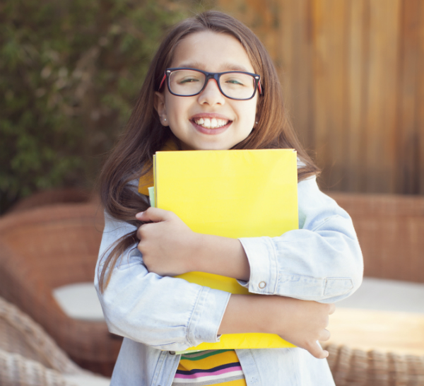 A female elementary student stands clutching a yellow folder to her chest and stomach.