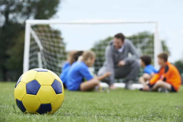 Students in with a soccer coach in the background of this picture, whilst a yellow soccer ball sits in the foreground.