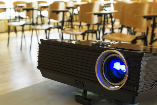 A projector sits on a table in a classroom.