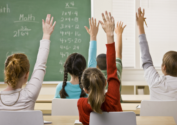 Students sit in math class with their hands raised, ready to answer a question.
