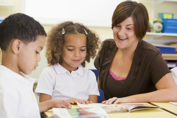 A teacher sits at a desk with two students, helping them read a book.