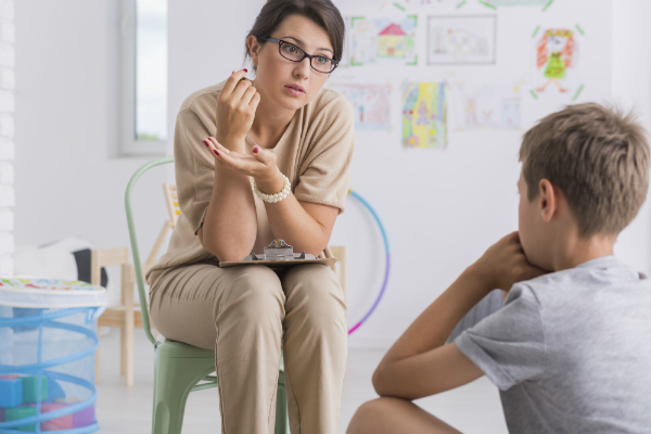 A teacher sits down with a misbehaving student, talking to him about his behavior as one of her classroom management strategies.