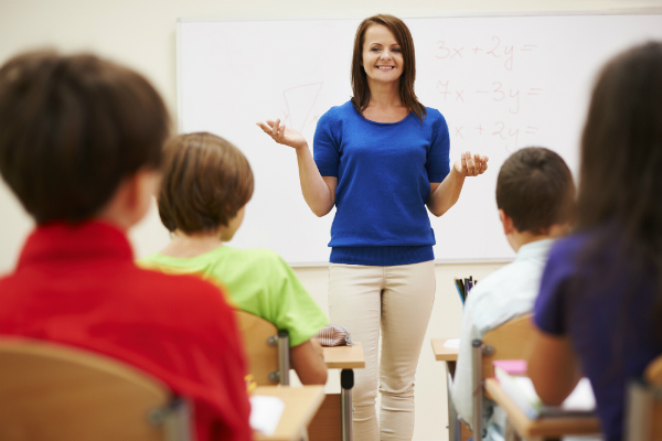 A teacher stands at the front of her class, trying to build excitement by previewing interesting parts of the day's lesson.