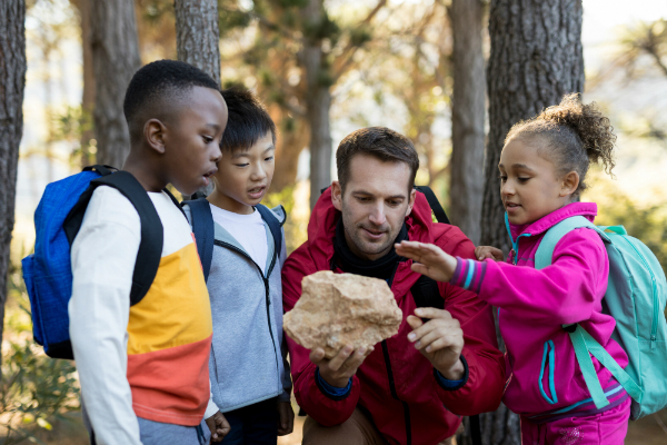 Three young elementary students gather around their teacher outside, who's showing and talking about a kind of rock.