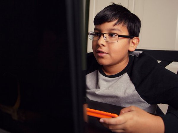 A child playing video games at his computer, which is an example of game-based learning