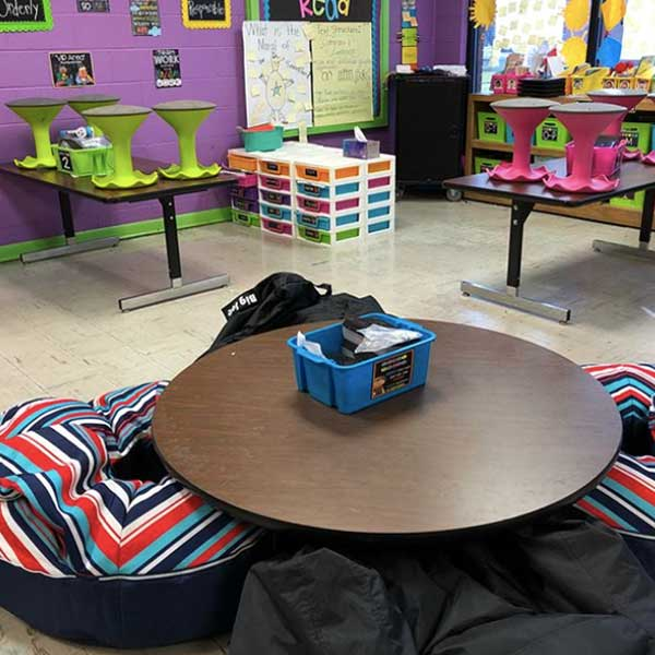 Flexible seating classroom with bean bag chairs around a low table.