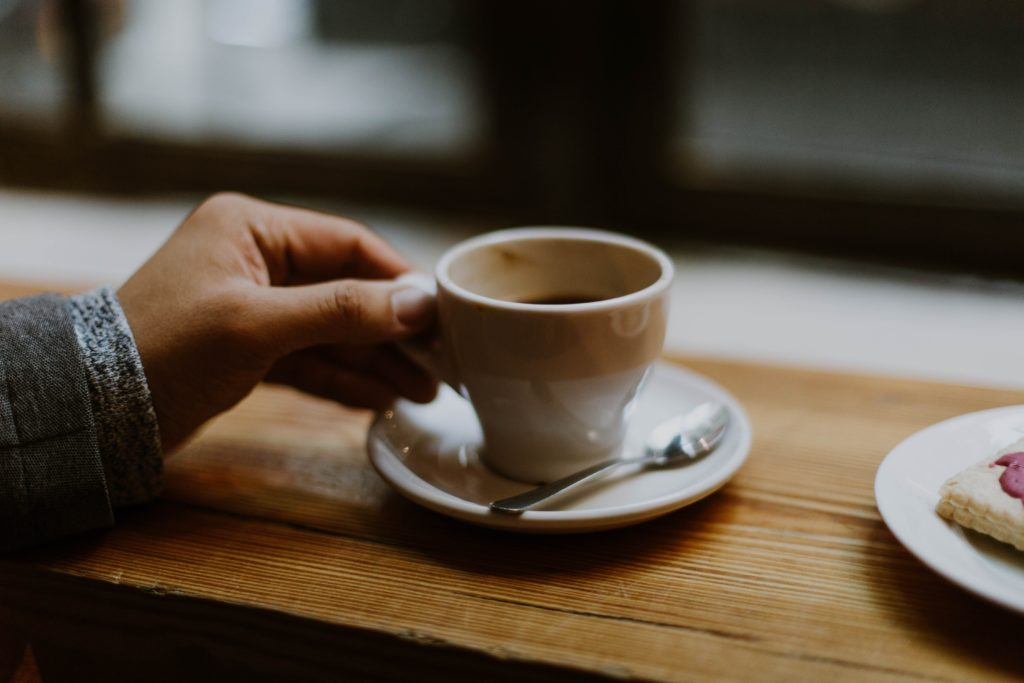 Hand holding a coffee cup.
