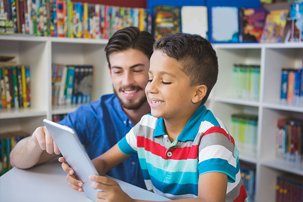 Meaningful report card comments start with a good in-class observation of student performance, as seen in this scene involving a student and teacher learning together with a tablet.
