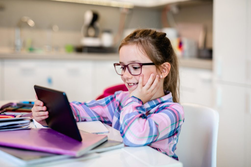 girl sitting at kitchen table looking at tablet and smiling