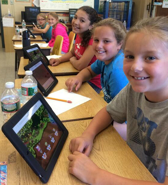 Four female elementary school students sit at a desk an play Prodigy, a math video game, on their tablets.