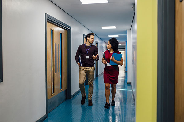 Two teachers walk down the hall, discussing report cards. Report card comments for struggling students are a challenge for many teachers to write.