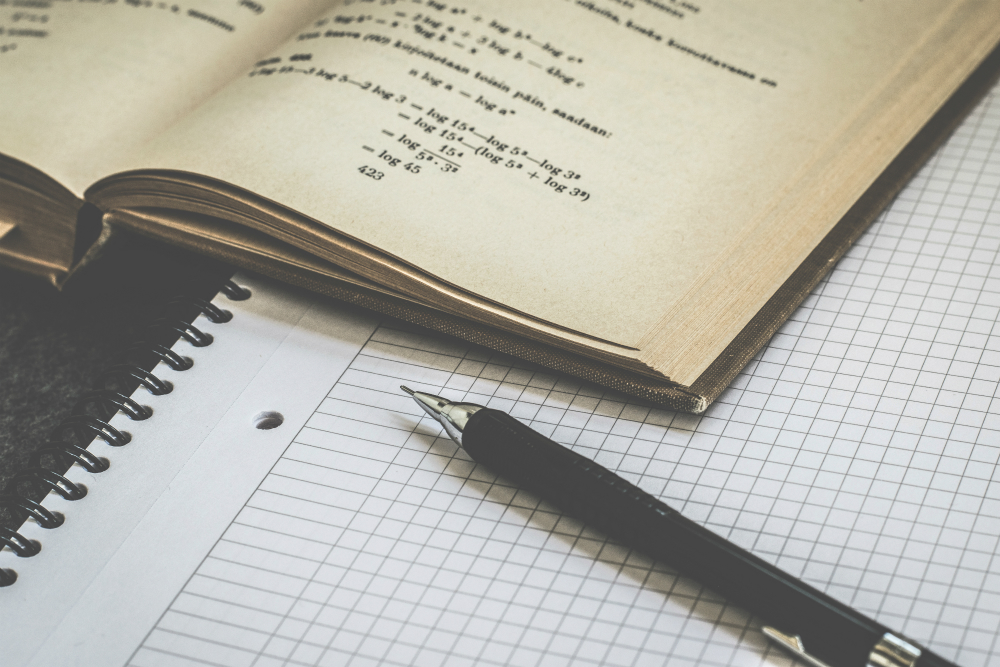 A pen and graph paper sits on a desk with an open math textbook.