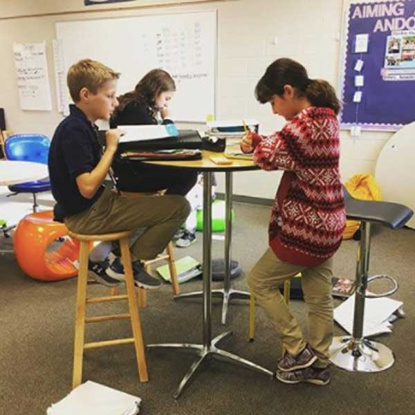students-standing-and-using-stools