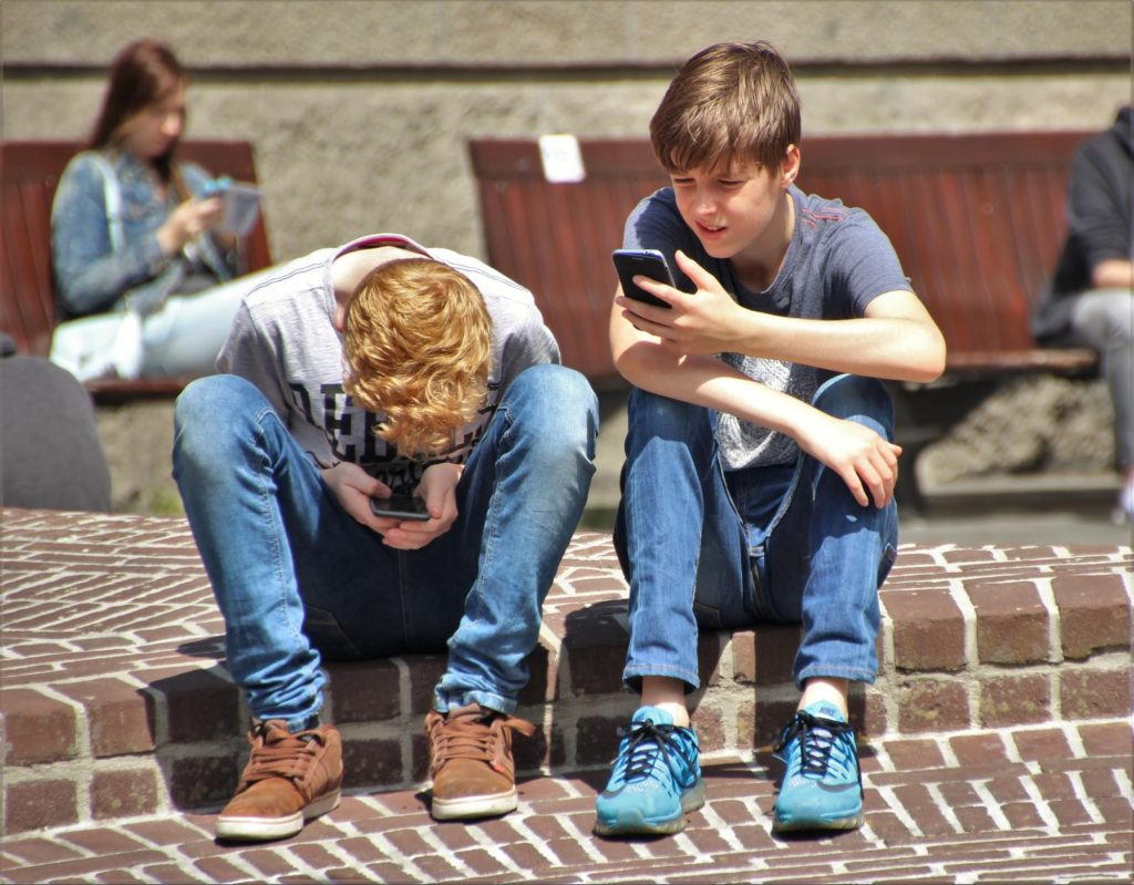 two teenagers and technology sitting outside