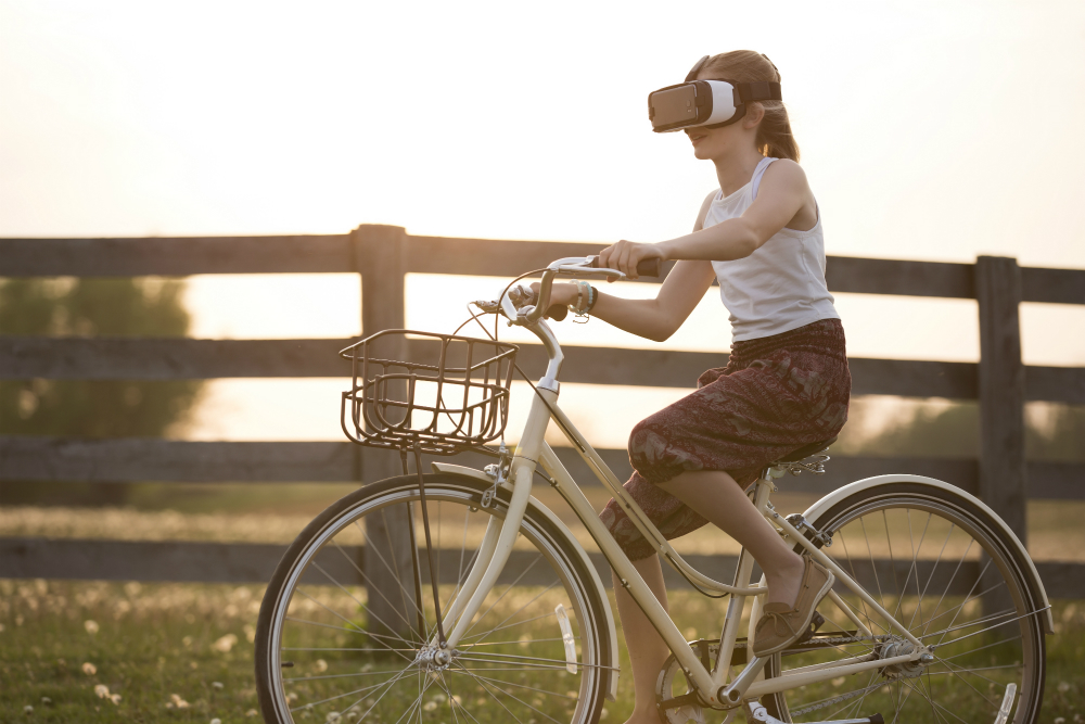 A girl rides her bike with a virtual reality headset on.
